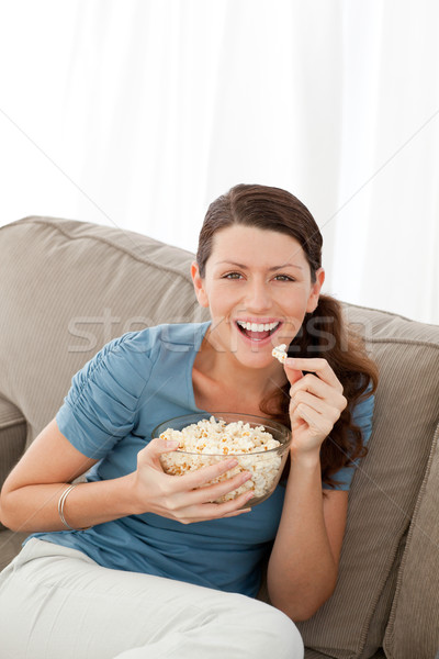 Portrait of a happy woman eating pop corn while watching television at home Stock photo © wavebreak_media