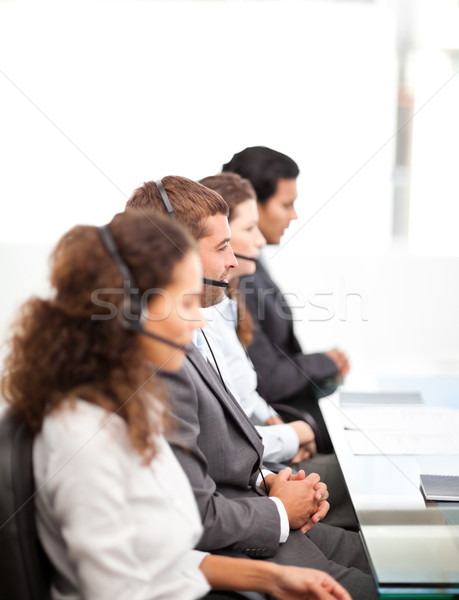 Four businesspeople on the phone sitting at their desk  in a row  Stock photo © wavebreak_media