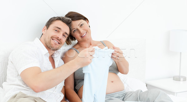 Young futur parents with chlidrens clothes at home Stock photo © wavebreak_media
