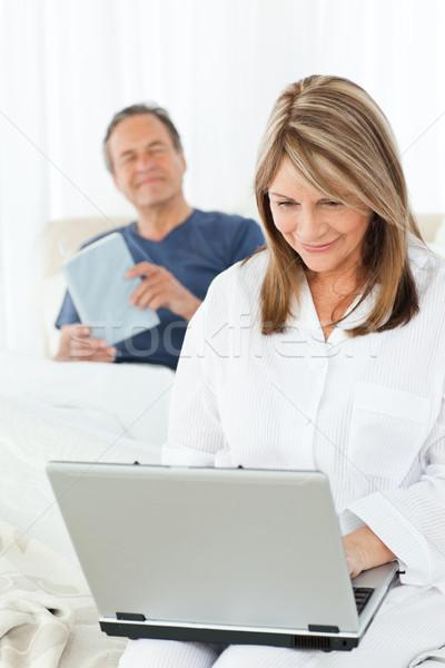 Mujer mirando portátil marido lectura cama Foto stock © wavebreak_media