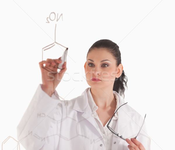 Dark-haired woman writting a formula on a white board in a lab Stock photo © wavebreak_media
