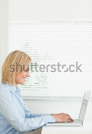 Beautiful woman having her breakfast while relaxing with a laptop in the kitchen Stock photo © wavebreak_media