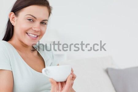 Közelkép bájos nő ül kanapé csésze Stock fotó © wavebreak_media