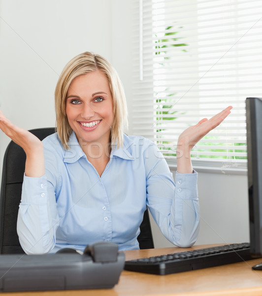 Smiling woman sitting behind desk not having a clue what to do next inan office Stock photo © wavebreak_media