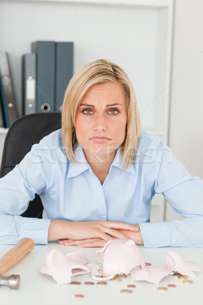 Sulking woman sitting in front of an shattered piggy bank looking into camera in her office Stock photo © wavebreak_media