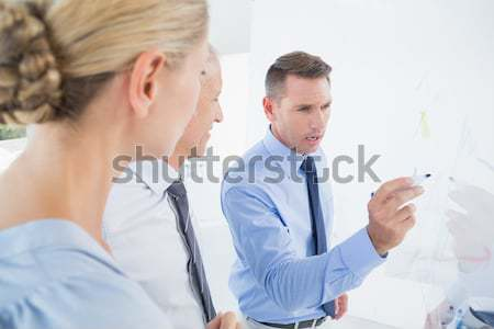 Businessman making a phone call while his colleague is posing against a white background Stock photo © wavebreak_media