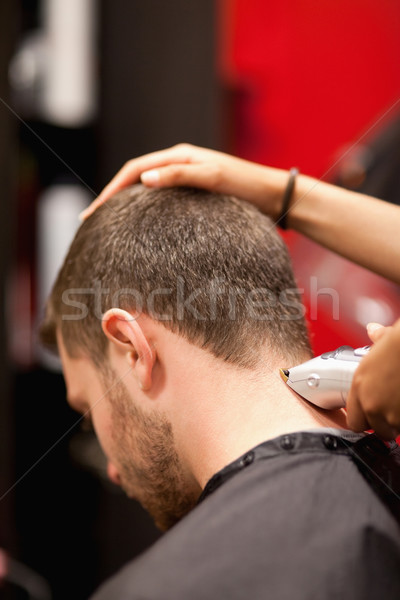 Portrait of a male young student having a haircut with a hair clippers Stock photo © wavebreak_media