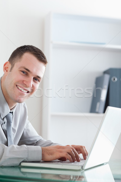 Smiling happy businessman typing on his laptop Stock photo © wavebreak_media