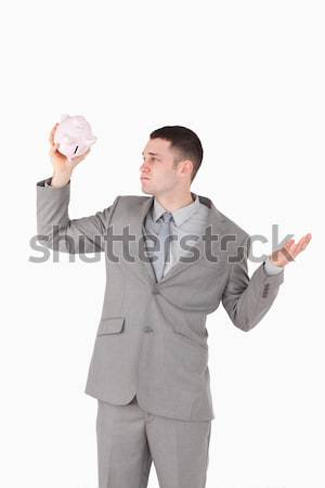 Portrait of a broke businessman looking at an empty piggy bank against a white background Stock photo © wavebreak_media