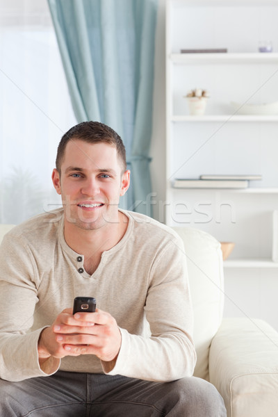 Portrait of a man sending text messages while sitting on a sofa in his living room Stock photo © wavebreak_media