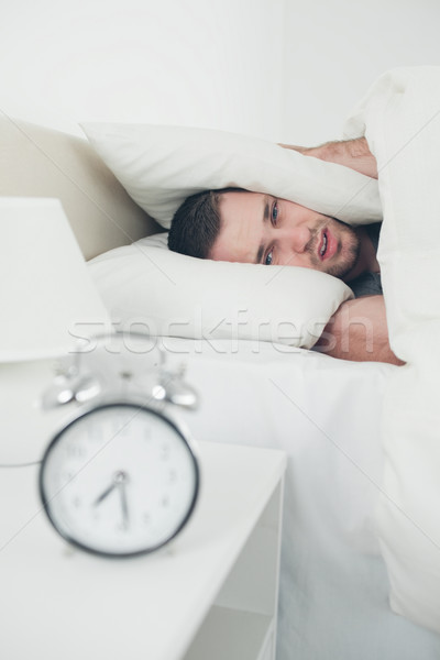 Portrait of a beautiful young man covering his ears while his alarm clock is ringing in his bedroom Stock photo © wavebreak_media