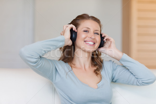 Sorridente mulher jovem fones de ouvido sofá soar sofá Foto stock © wavebreak_media