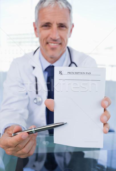 Portrait of a doctor showing a blank prescription sheet in his office Stock photo © wavebreak_media
