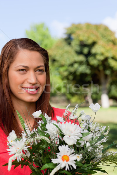 Woman looking towards the side while holding a bunch of flowers and and standing in an open area sur Stock photo © wavebreak_media