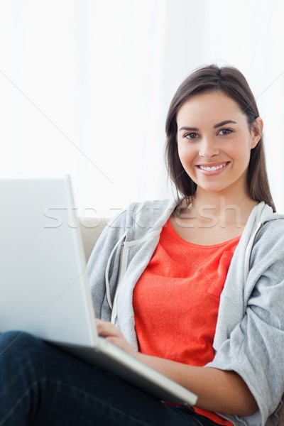 A woman smiling brightly while looking at the camera and using her laptop Stock photo © wavebreak_media