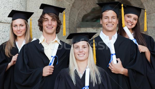 Close-up of five happy graduates posing in front of the university Stock photo © wavebreak_media