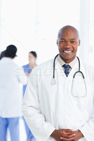 Smiling intern wearing a tie under his white lab coat Stock photo © wavebreak_media