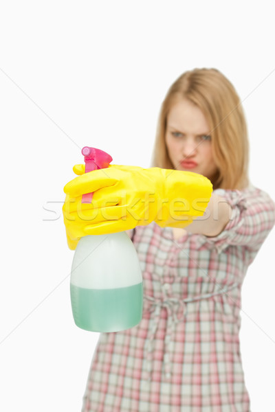 Young woman holding a spray bottle against white background Stock photo © wavebreak_media