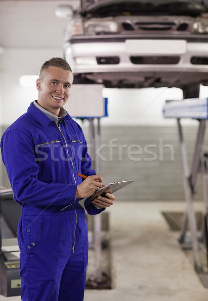Smiling mechanic writing on a clipboard in a garage Stock photo © wavebreak_media