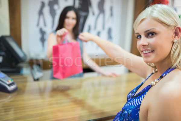 Woman taking bag at cash register in clothing store Stock photo © wavebreak_media