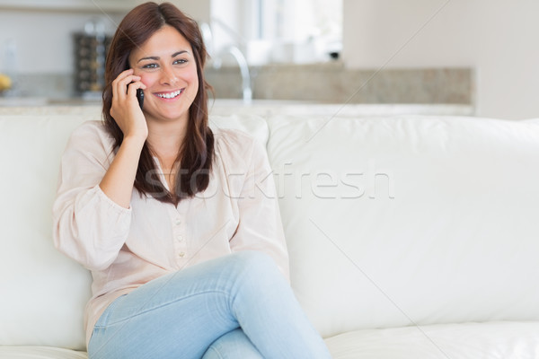 Woman phoning while sitting on the couch in the living room Stock photo © wavebreak_media