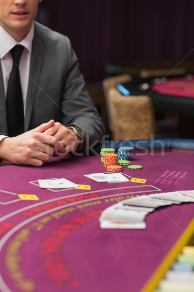 Man sitting at poker tabe with cards and chips in casino Stock photo © wavebreak_media
