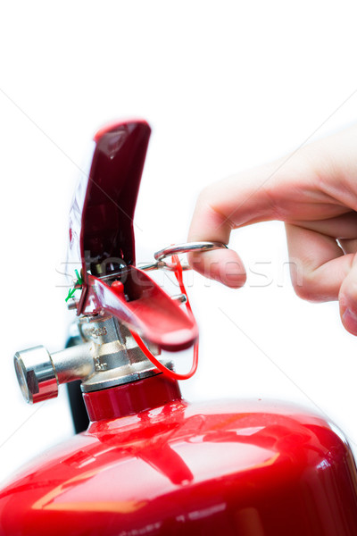 Hand pulling safety pin from red fire extinguisher Stock photo © wavebreak_media
