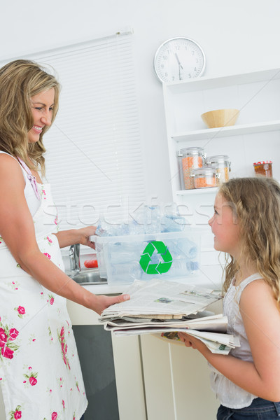 Smiling mother taking old newspaper from daughter for recycling Stock photo © wavebreak_media