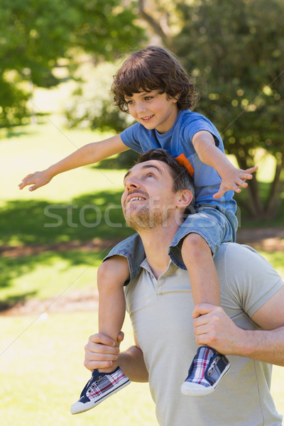 Stock photo: Smiling man carrying son on his shoulders in park