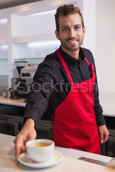 Smiling young barista putting cup of coffee down on counter Stock photo © wavebreak_media