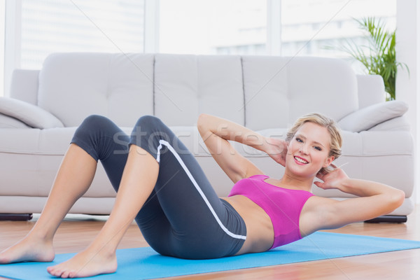 Slim blonde doing sit ups on exercise mat smiling at camera Stock photo © wavebreak_media