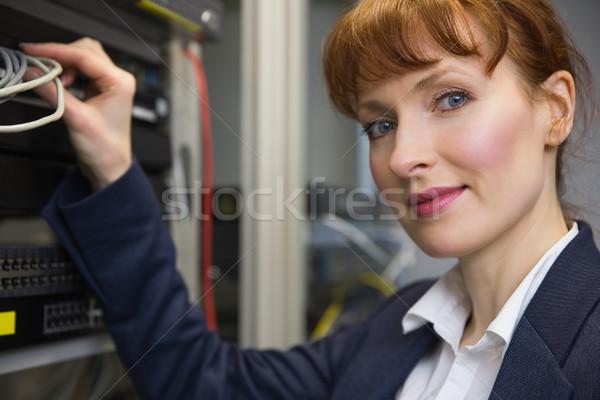 Pretty computer technician smiling at camera while fixing server Stock photo © wavebreak_media
