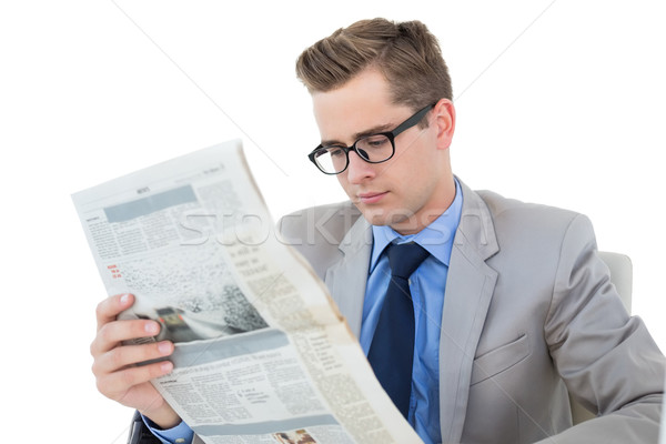 Stock photo: Nerdy businessman reading the newspaper