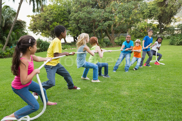 Cute pupils playing tug of war on the grass outside  Stock photo © wavebreak_media