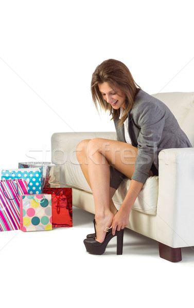 Young woman sitting on couch taking off her shoes Stock photo © wavebreak_media