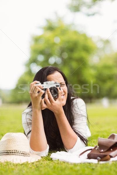 Smiling brunette lying on grass taking picture Stock photo © wavebreak_media
