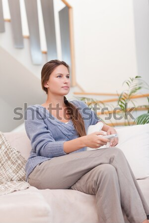 Smiling blonde changing tv channel while eating popcorn Stock photo © wavebreak_media