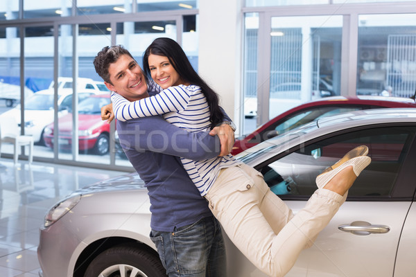 Stock photo: Smiling couple hugging and smiling at camera