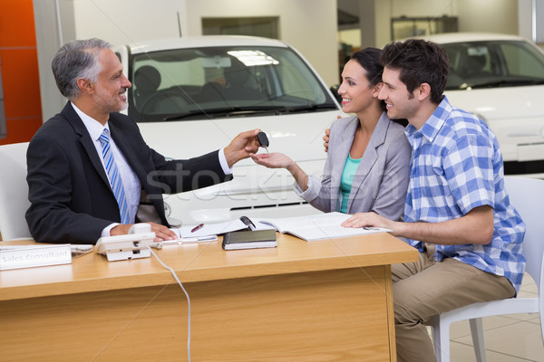 Salesman giving car keys to a couple Stock photo © wavebreak_media