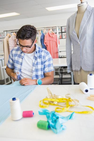 Fashion student cutting fabric with pair of scissors Stock photo © wavebreak_media