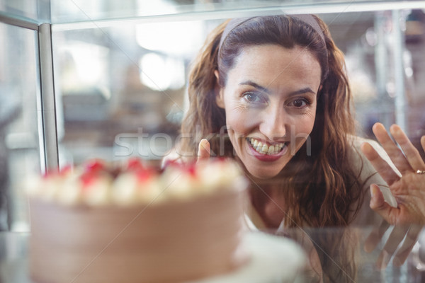 Pretty brunette looking at chocolate cake through the glass Stock photo © wavebreak_media