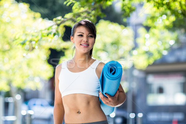 Smiling athletic woman carrying yoga mat Stock photo © wavebreak_media