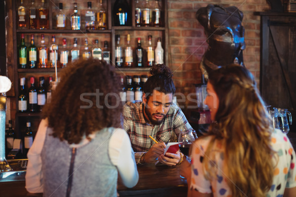 Bartender taking an order on notepad at counter Stock photo © wavebreak_media