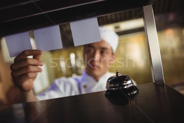 Chef olhando ordem lista comercial cozinha Foto stock © wavebreak_media