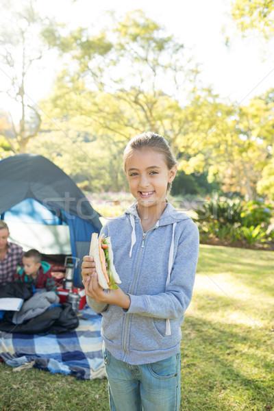 Mosolyog lány tart szendvics táborhely portré Stock fotó © wavebreak_media