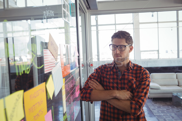 Stock photo: Thoughtful businessman looking at adhesive notes in office