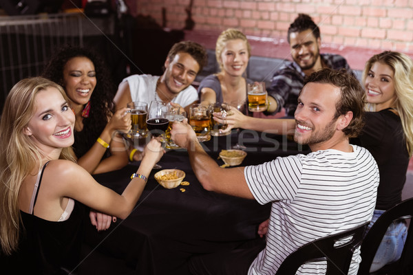 Portrait of smiling friends toasting drinks while sitting together at nightclub Stock photo © wavebreak_media