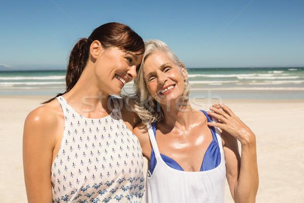 Happy mother and daughter standing on beach Stock photo © wavebreak_media