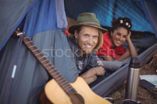 Sorridente casal relaxante tenda retrato floresta Foto stock © wavebreak_media