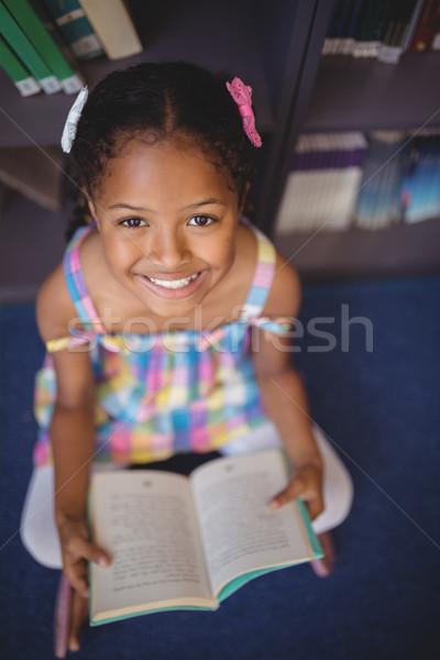портрет улыбаясь школьница чтение книга библиотека Сток-фото © wavebreak_media